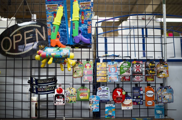 "International calling cards and toys rest on a wall at the El Mercado Market in what is locally known as ""Kimmeytown"", an area of Georgetown, Delaware on November 6, 2014. Georgetown is home to more than 2,500 Hispanic residents, which became a Guatemalan enclave beginning in the 1990's. (Jim Watson/AFP/Getty Images)"