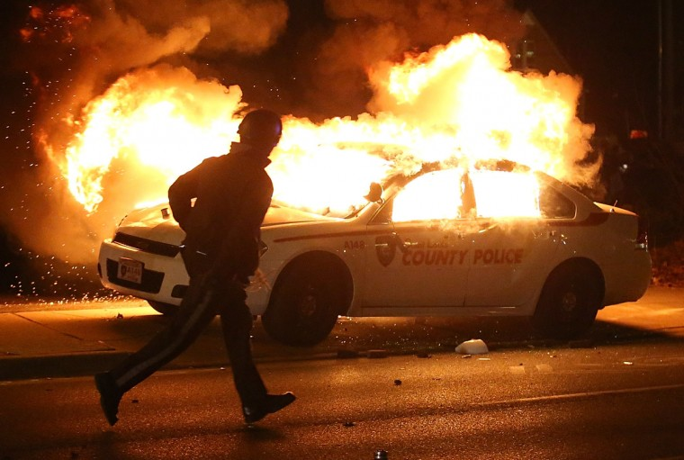 A police officer runs by a burning police car during a demonstration on November 24, 2014 in Ferguson, Missouri. A St. Louis County grand jury has decided to not indict Ferguson police Officer Darren Wilson in the shooting of Michael Brown that sparked riots in Ferguson, Missouri in August. (Justin Sullivan/Getty Images)