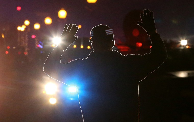 A protestor stands in front of police vehicles with his hands up during a demonstration on November 24, 2014 in Ferguson, Missouri. A St. Louis County grand jury has decided to not indict Ferguson police Officer Darren Wilson in the shooting of Michael Brown that sparked riots in Ferguson, Missouri in August. (Justin Sullivan/Getty Images)