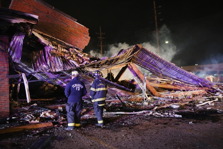 Ferguson firefighters survey rubble at a strip mall that was set on fire when rioting erupted following the grand jury announcement in the Michael Brown case on November 25, 2014 in Ferguson, Missouri. Brown, an 18-year-old black man, was killed by Darren Wilson, a white Ferguson police officer, on August 9. At least 12 buildings were torched and more than 50 people were arrested during the night-long rioting. (Photo by Scott Olson/Getty Images)