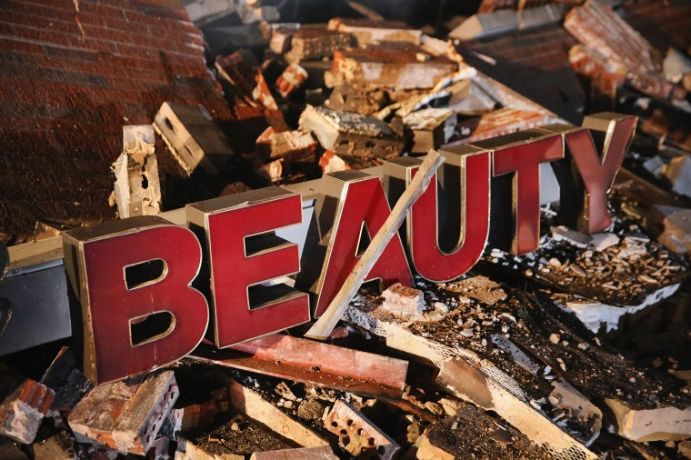 A sign rests in the rubble of a strip mall that was set on fire when rioting erupted following the grand jury announcement in the Michael Brown case on November 25, 2014 in Ferguson, Missouri. Brown, an 18-year-old black man, was killed by Darren Wilson, a white Ferguson police officer, on August 9. At least 12 buildings were torched and more than 50 people were arrested during the night-long rioting. (Photo by Scott Olson/Getty Images)