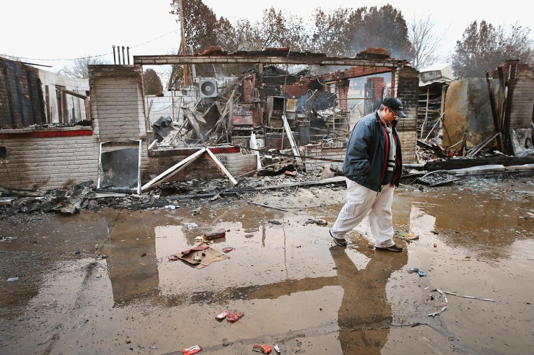 Property manager Terri Willits looks over a gas station she manages that was set on fire when rioting erupted following the grand jury announcement in the Michael Brown case on November 25, 2014 in Dellword Missouri. Brown, an 18-year-old black man, was killed by Darren Wilson, a white Ferguson police officer, on August 9. At least 12 buildings were torched and more than 50 people were arrested during the night-long rioting. (Photo by Scott Olson/Getty Images)