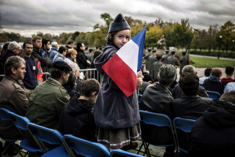 "A young girl dressed as a ""poilu"", a World War I-era French soldier, holds a French flag during Armistice Day ceremonies marking the 96th anniversary of the end of WWI, on November 11, 2014 in Lyon. (Jeff Pachoud/AFP/Getty Images)"