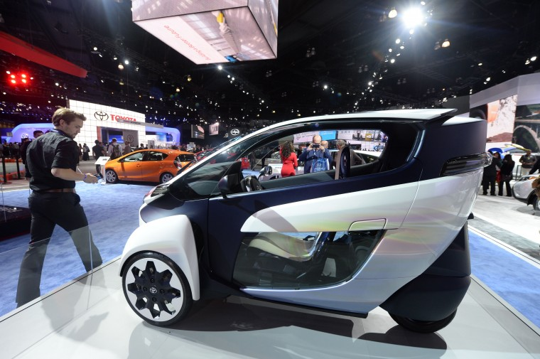 A visitor passes the Toyota i-Road concept vehicle for urban mobility at the Los Angeles Auto Show media preview days, November 19, 2014 in Los Angeles, California. (Robyn Beck/AFP/Getty Images)