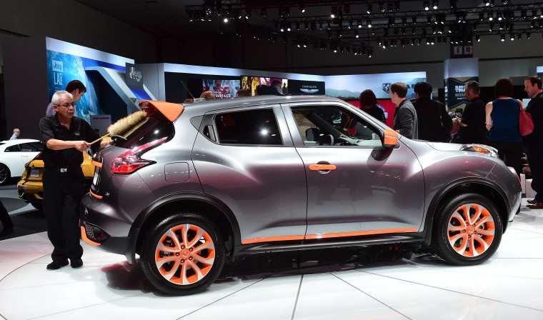 A man dusts the rear window of a 2015 Nissan Juke on display at the LA Auto Show's press and trade day in Los Angeles, California on November 20, 2014. The LA Auto Show which opens to the public on November 21 and will run until November 30. (Frederic J. Brown/AFP/Getty Images)