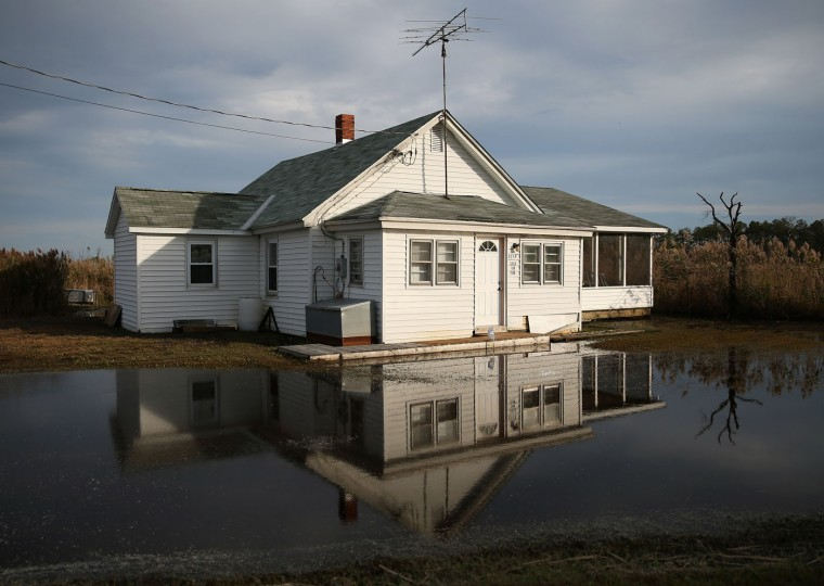 The front yard of a vacant home is flooded from rising ground water October 9, 2014 in Robbins, Maryland. Several islands and property's located at sea level in the lower Chesapeake Bay region are slowly eroding away as sea levels rise. Officials have projected the sea level will rise several feet over the next century leaving many of the Chesapeake bay's lower islands underwater. (Photo by Mark Wilson/Getty Images)