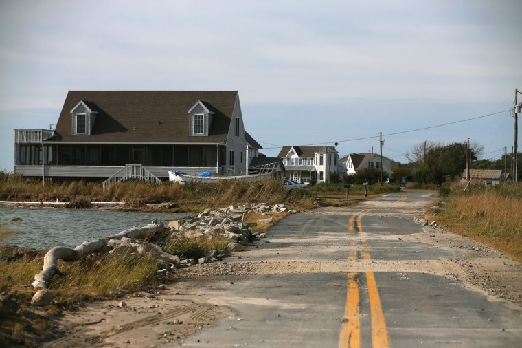 Sand from a recent high tide covers a road near a home with an eroded septic field, October 9, 2014 in Hoppers Island, Maryland. Several islands and property's located at sea level in the lower Chesapeake Bay region are slowly eroding away as sea levels rise. Officials have projected the sea level will rise several feet over the next century leaving many of the Chesapeake bay's lower islands underwater. (Photo by Mark Wilson/Getty Images)