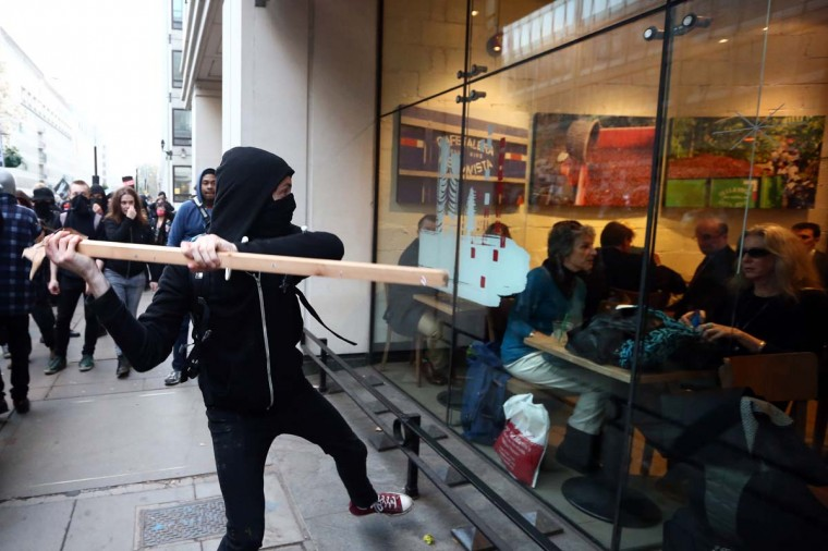 A protester attempts to smash a Starbucks window during a demonstration against fees and cuts in the education system on November 19, 2014 in London, England. A coalition of student groups have organized a day of nationwide protests in support of free education and to campaign against cuts. Photo by Carl Court/Getty Images) (Carl Court/Getty Images)