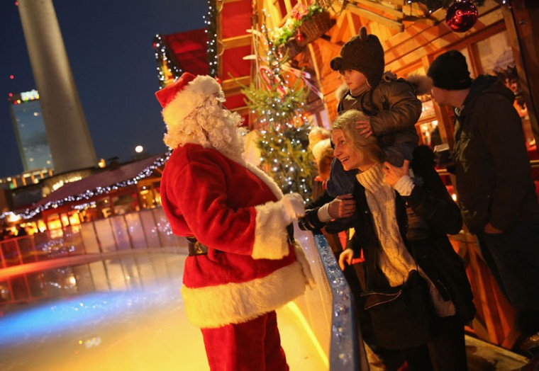 Gaspard, 3, and his mother Anne get a visit from Santa Claus at an ice-skating rink at the Christmas market at Alexanderplatz on the market's opening day on November 24, 2014 in Berlin, Germany. Christmas markets across Germany will open this week and stay open through the end of December to sell Gluehwein, Christmas decorations, sweets and other delights. (Sean Gallup/Getty Images)