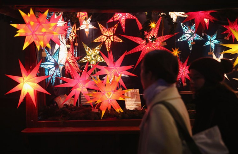 Visitors walk past a stall selling illuminated Christmas stars at the Christmas market at Alexanderplatz on the market's opening day on November 24, 2014 in Berlin, Germany. Christmas markets across Germany will open this week and stay open through the end of December to sell Gluehwein, Christmas decorations, sweets and other delights in an annual tradition. (Sean Gallup/Getty Images)