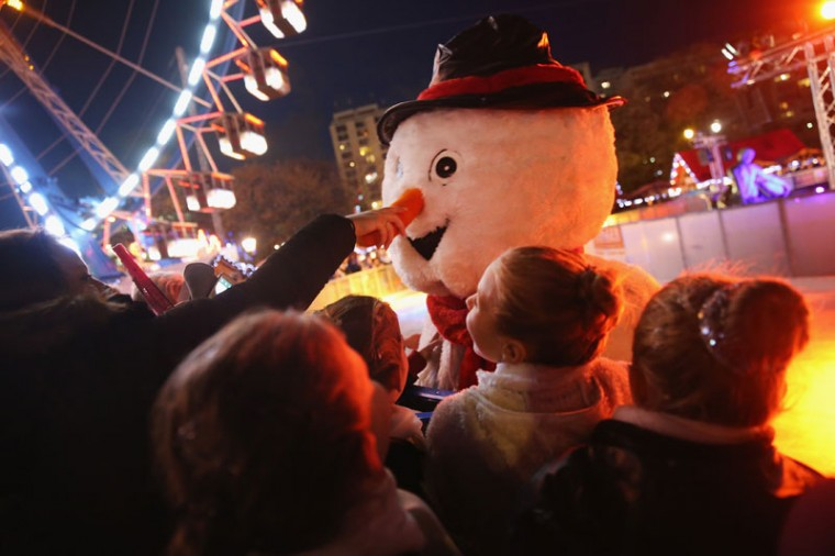 A visitor gives a tug on the carrot nose of a snowman on ice skates at the Christmas market at Alexanderplatz on the market's opening day on November 24, 2014 in Berlin, Germany. Christmas markets will open across Germany this week and stay open through the end of December to sell Gluehwein, Christmas decorations, sweets and other delights in an annual tradition. (Sean Gallup/Getty Images)