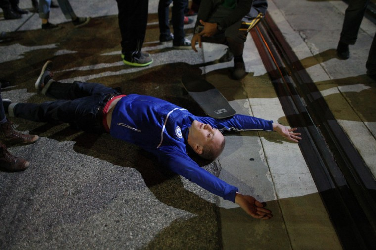 A man lies near railroad tracks as protesters block a trolly following the grand jury decision not to indict a white police officer who had shot dead an unarmed black teenager in Ferguson, Missouri on the night of November 25, 2014 in Los Angeles, California. Police officer Darren Wilson shot 18-year-old Michael Brown on August 9, sparking large ongoing protests. (Photo by David McNew/Getty Images)
