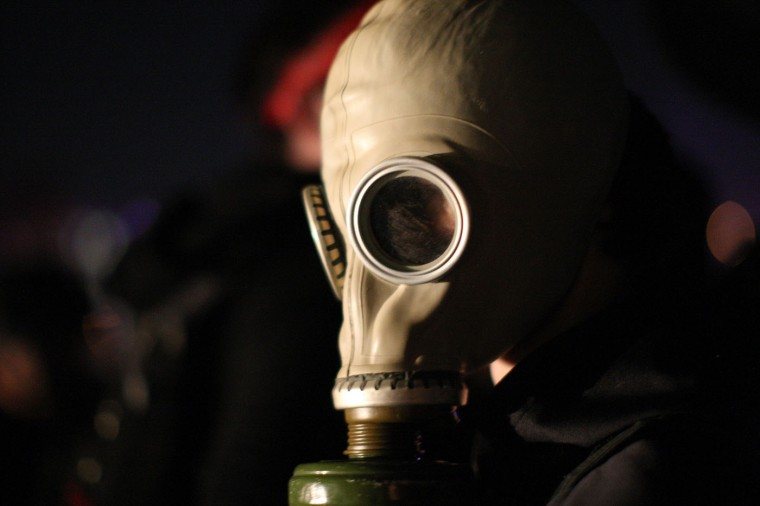 A protester puts on a gas mask when a large group of protesters are blocked in on all sides by police on an over ramp after protesters ran on to, and blockaded, the 101 freeway following the grand jury decision not to indict a white police officer who had shot dead an unarmed black teenager in Ferguson, Missouri on the night of November 25, 2014 in Los Angeles, California. Police officer Darren Wilson shot 18-year-old Michael Brown on August 9, sparking large ongoing protests. (Photo by David McNew/Getty Images)