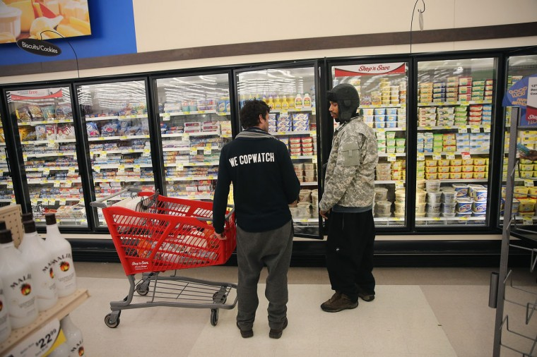 David Whitt (R) and Jacob Crawford shop groceries for Thanksgiving dinner on Thanksgiving Day November 27, 2014 near Ferguson, Missouri. Whitt lives in the Canfield Green Apartments near where Michael Brown was killed. Crawford works with Copwatch an organization that monitors police activity in neighborhoods. Whitt started a Copwatch chapter in Ferguson after Brown was killed. The Ferguson area has been struggling to return to normal since the August 9 shooting of Brown, an 18-year-old black man, who was killed by Darren Wilson, a white Ferguson police officer. Monday, when the grand jury announced that Wilson would not face charges in the shooting, rioting and looting broke out throughout the area. (Photo by Scott Olson/Getty Images)