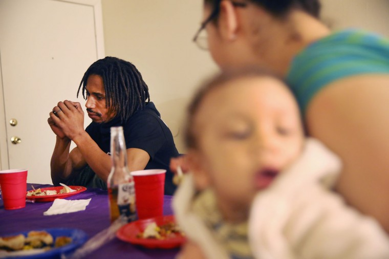 David Whitt sits down for a Thanksgiving dinner with his wife Aurellia and son Byron on November 27, 2014 in Ferguson, Missouri. Whitt and his family live in the Canfield Green Apartments near where Michael Brown was killed. The Ferguson area has been struggling to return to normal since the August 9 shooting of Brown, an 18-year-old black man, who was killed by Darren Wilson, a white Ferguson police officer. Monday, when the grand jury announced that Wilson would not face charges in the shooting, rioting and looting broke out throughout the area. (Photo by Scott Olson/Getty Images)