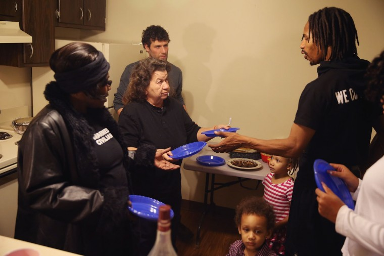 Residents of Canfield Green Apartments, where Michael Brown was killled, gather for a Thanksgiving dinner on November 27, 2014 in Ferguson, Missouri. The Ferguson area has been struggling to return to normal since the August 9 shooting of Brown, an 18-year-old black man, who was killed by Darren Wilson, a white Ferguson police officer. Monday, when the grand jury announced that Wilson would not face charges in the shooting, rioting and looting broke out throughout the area. (Photo by Scott Olson/Getty Images)