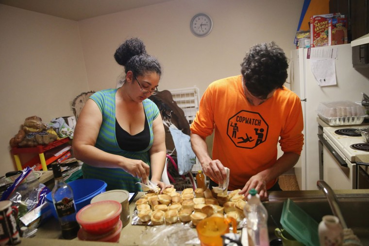 Aurellia Davis (L) and Jacob Crawford prepare Thanksgiving dinner at Davis's home in the Canfield Green Apartments where Michael Brown was killed on November 27, 2014 in Ferguson, Missouri. Crawford works with Copwatch an organization that monitors police activity in neighborhoods. Davis' husband David Whitt started a Copwatch chapter in Ferguson after Brown was killed.The Ferguson area has been struggling to return to normal since the August 9 shooting of Brown, an 18-year-old black man, who was killed by Darren Wilson, a white Ferguson police officer. Monday, when the grand jury announced that Wilson would not face charges in the shooting, rioting and looting broke out throughout the area. (Photo by Scott Olson/Getty Images)