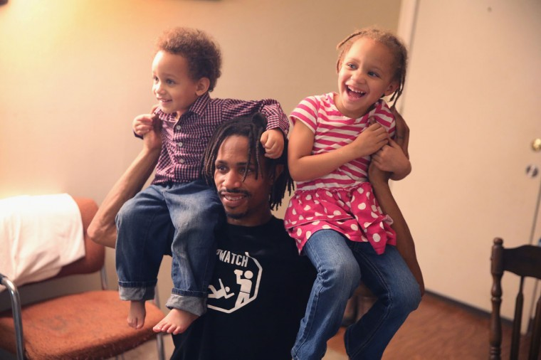 David Whitt plays with his children David Jr. (L) and Aurolla while preparing Thanksgiving dinner with his wife at their home in the Canfield Green Apartments where Michael Brown was killed on November 27, 2014 in Ferguson, Missouri. The Ferguson area has been struggling to return to normal since the August 9 shooting of Brown, an 18-year-old black man, who was killed by Darren Wilson, a white Ferguson police officer. Monday, when the grand jury announced that Wilson would not face charges in the shooting, rioting and looting broke out throughout the area. (Photo by Scott Olson/Getty Images)