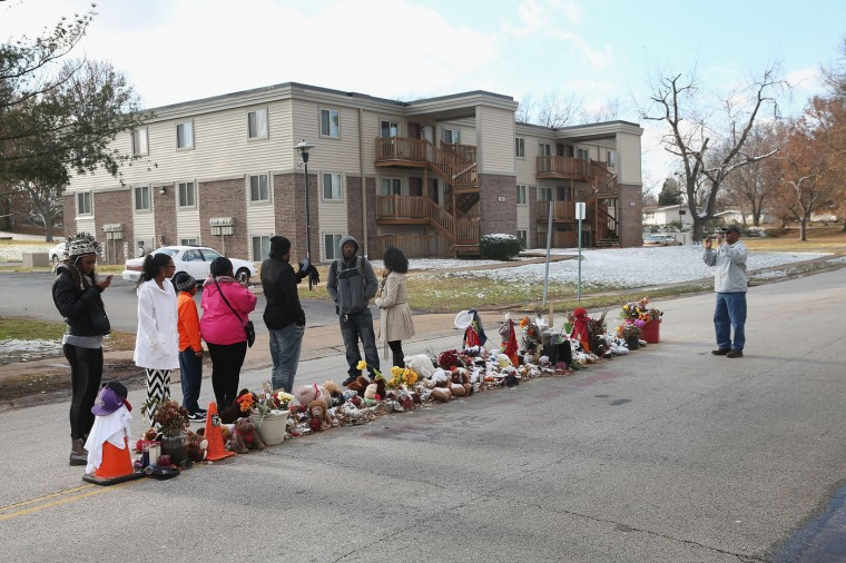 A family visits the Michael Brown memorial in the Canfield Green Apartments on Thanksgiving Day on November 27, 2014 in Ferguson, Missouri. The Ferguson area has been struggling to return to normal since the August 9 shooting of Brown, an 18-year-old black man, who was killed by Darren Wilson, a white Ferguson police officer. Monday, when the grand jury announced that Wilson would not face charges in the shooting, rioting and looting broke out throughout the area. (Photo by Scott Olson/Getty Images)