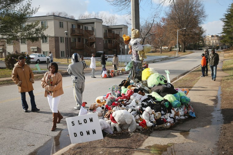 People visit the Michael Brown memorial in the Canfield Green Apartments on Thanksgiving Day on November 27, 2014 in Ferguson, Missouri. The Ferguson area has been struggling to return to normal since the August 9 shooting of Brown, an 18-year-old black man, who was killed by Darren Wilson, a white Ferguson police officer. Monday, when the grand jury announced that Wilson would not face charges in the shooting, rioting and looting broke out throughout the area. (Photo by Scott Olson/Getty Images)