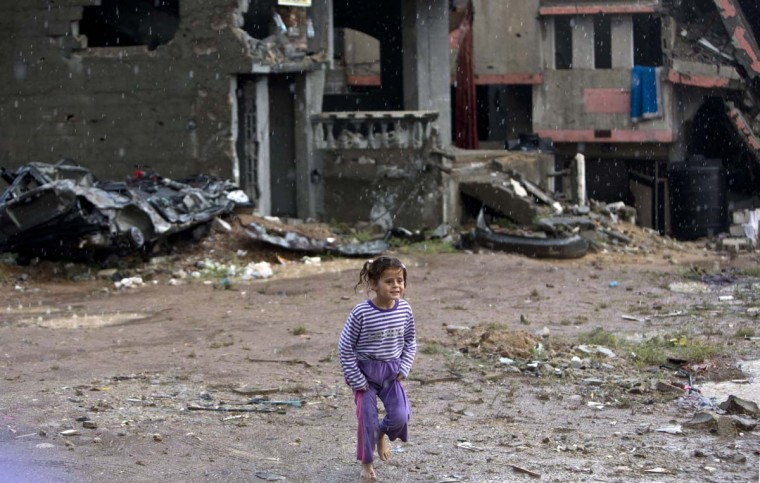 A Palestinian girl plays in the rain next to the rubble of buildings destroyed during the 50 days of conflict between Israel and Hamas last summer, in the Shejaiya neighborhood of Gaza City on November 3, 2014. (Mahmud Hams/AFP/Getty Images)