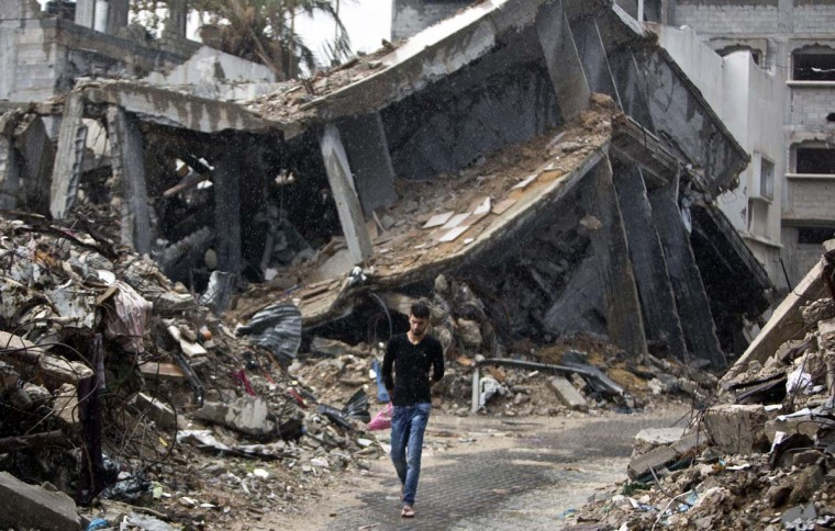 A Palestinian man walks in the rain next to the rubble of buildings destroyed during the 50 days of conflict between Israel and Hamas last summer, in the Shejaiya neighborhood of Gaza City on November 3, 2014. (Mahmud Hams/AFP/Getty Images)