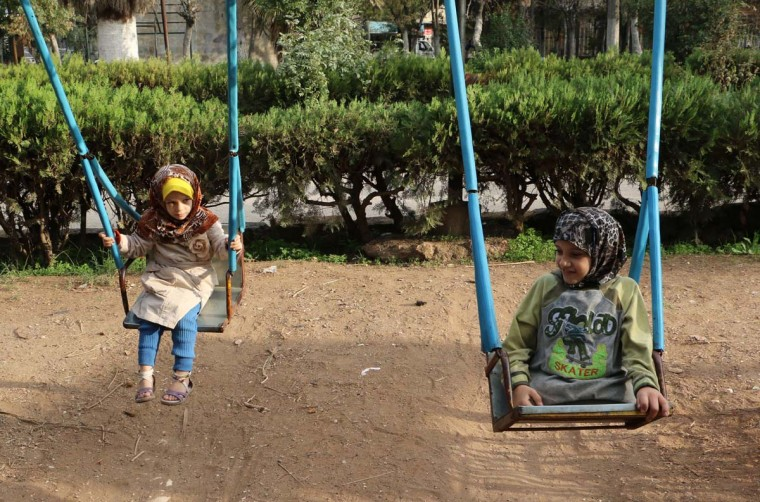 Sharouk (R), a nine-year old Syrian girl, who lost her legs after a shell hit her house, plays on a swing with another child in a park in the northern Syrian city of Aleppo on November 3, 2014. Thousands of Syrian children have been killed in the conflict that began in March 2011, and many more have been displaced by the fighting between regime forces and the rebels. (Baraa Al-Halabi/AFP/Getty Images)