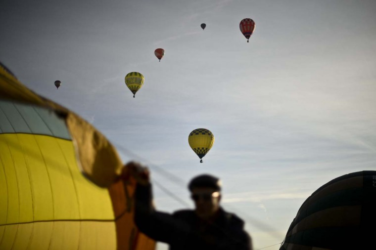 A balloonist prepares his balloon while others fly during the 18th International Festival of Hot Air Balloons in Alter do Chao in the center of Portugal on November 10, 2014. (Patricia De Melo Moreira/AFP/Getty Images)
