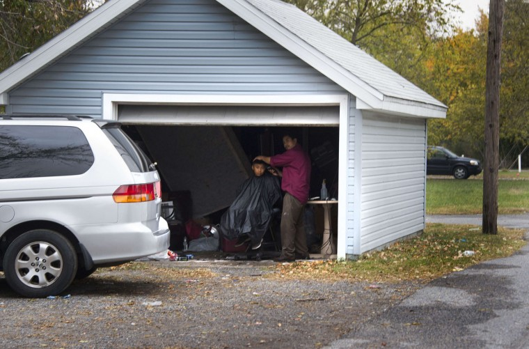 "A Latin American man cuts his son's hair in the garage in what is locally known as ""Kimmeytown"", an area of Georgetown, Delaware on November 6, 2014. Georgetown is home to more than 2,500 Hispanic residents, which became a Guatemalan enclave beginning in the 1990's. (Jim Watson/AFP/Getty Images)"