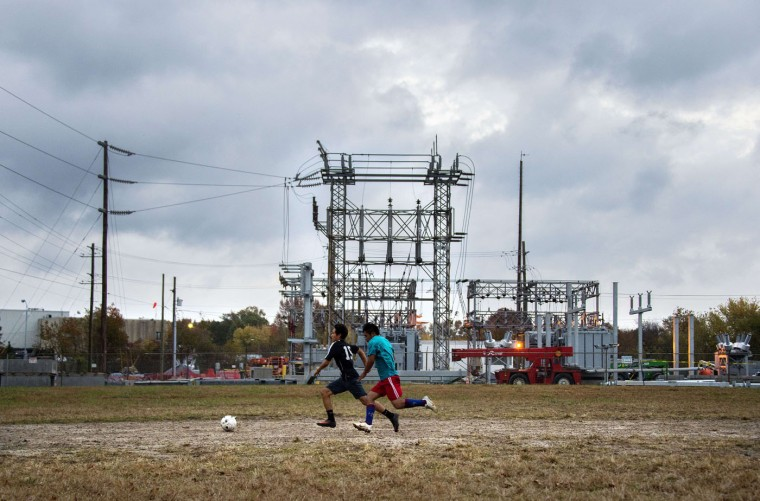 "Local boys play soccer on a dirt field behind the Perdue chicken processing plant in what is locally known as ""Kimmeytown"", an area of Georgetown, Delaware on November 6, 2014. Georgetown is home to more than 2,500 Hispanic residents, which became a Guatemalan enclave beginning in the 1990's. (Jim Watson/AFP/Getty Images)"