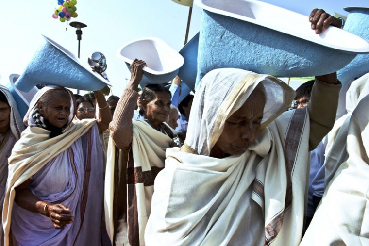 Indian women carry toilets on their heads as they participate in the opening ceremony of the three-day International Toilet Festival in New Delhi on November 18, 2014, the eve of World Toilet Day. UNICEF estimates that almost 594 million -- or nearly 50 percent of India's population -- defecate in the open, with the situation acute in dirt-poor rural areas. Some 300 million women and girls are forced to squat outside normally under the cover of darkness, exposed not only to the risks of disease and bacterial infection, but also harassment and assault by men. (Roberto Schmidt/AFP/Getty Images)