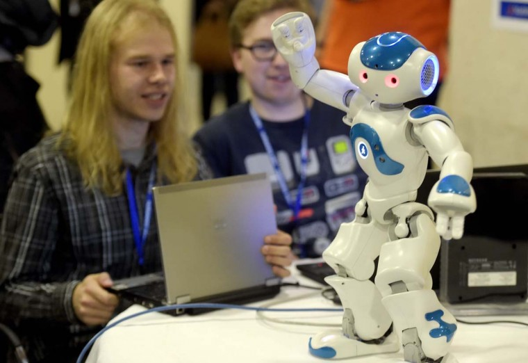 "Programmers work on their laptop past ""NAO"", a programmable humanoid robot developed by French robotics company Aldebaran Robotics during the 2014 IEEE-RAS International Conference on Humanoid Robots in Madrid on November 19, 2014. The conference theme ""Humans and Robots Face-to-Face"" confirms the growing interest in the field of human-humanoid interaction and cooperation, especially during daily life activities in real environments. (Gerard Julien/AFP/Getty Images)"