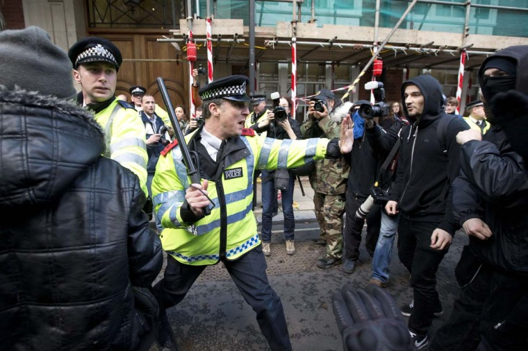 A police officer clashes with protesters outside the Conservative Campaign Headquarters after a march against student university fees in central London on November 19, 2014. The demonstration organized by the Student Assembly Against Austerity, alongside the Young Greens and National Campaign Against Fees and Cuts demands free education and an end to tuition fees, education cuts and student debt. (Justin Tallis/AFP/Getty Images)