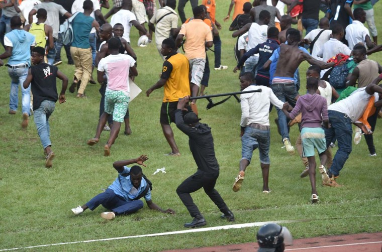A policeman beats a man as people run on the pitch at the Felix Houphouet-Boigny Stadium in Abidjan on November 19, 2014 at the end of the 2015 Africa Cup of Nations group D qualifying football match between Ivory Coast and Cameroon. (Issouf Sanogo//AFP/Getty Images)