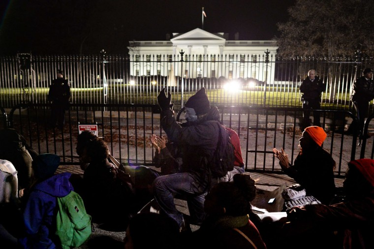 Protesters sit on the ground outside the White House in Washington, DC on November 25, 2014, during a protest rally, one day after a grand jury decision not to prosecute a white police officer for the killing of an unarmed black teen in Ferguson, Missouri. Mladen Antonov/AFP/Getty Images