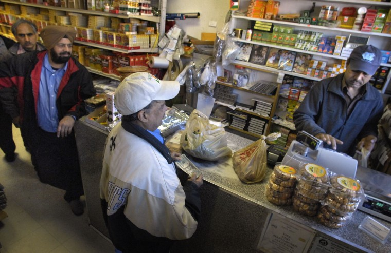 12/25/07: Employee Mohammad Arshad, at right, rings up the order for customer John Fernando, in front, as other customers, Mohammad Sainsara, far left, and Sher Singh, second from left, wait their turn. Punjab Halal Meat and Groceries store on 33rd St. in Waverly, which specializes in Indian foodstuffs is one of the businesses that is open on Christmas Day. (Amy Davis/Baltimore Sun)