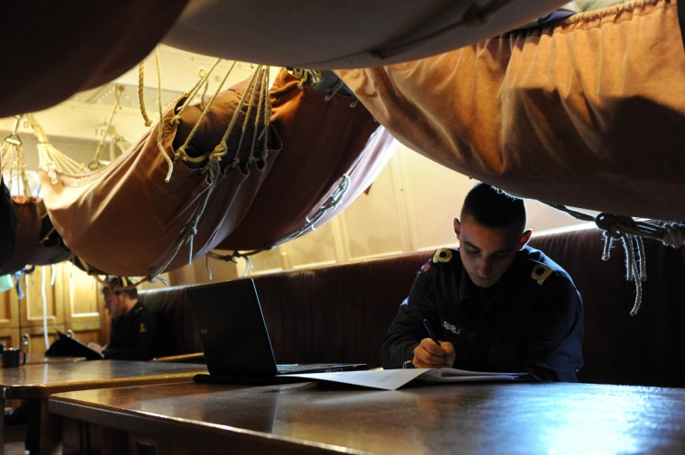 Michael Sorli, 21, Bergen, Norway, records personal reflections on the trip on the HNoMS Statsraad Lehmkuhl, a training vessel for the Norwegian Navy. Hammocks hang over head in the aft accommodation room. Kim Hairston/Baltimore Sun