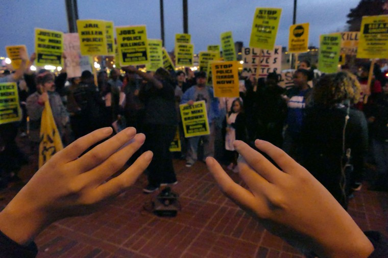 Tanya Garcia of Baltimore holds up her hands with the rest of the group during a protest resulting from the recent decision by a grand jury citing lack of sufficient evident to prosecute an officer for the fatal shooting of an unarmed teenager in Ferguson, Mo. Karl Merton Ferron / Baltimore Sun