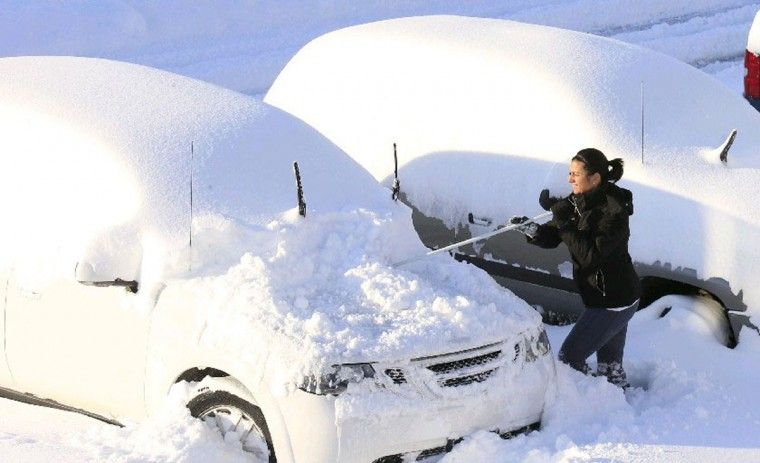 Christine Bloom work to clear her SUV to try and make it to work in Hamburg, N.Y. on Nov. 19, 2014. (Harry Scull Jr./Buffalo News)