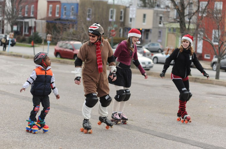"12/15/12: Asa Arnold, 4, of Evergreen, left, looks up to Jen Litsinger ""Bianca Dunk"" with the Charm City Roller Girls as they skate with fellow CCRG members Hilary Parker ""Status: Bitchin'"" and Lily Bradford ""Ace Hellcat, right, during a Skate and Scoot with Santa event at the Waverly Farmers Market in Baltimore, Md., on Saturday, December 15, 2012. (Brian Krista/Sun file)"