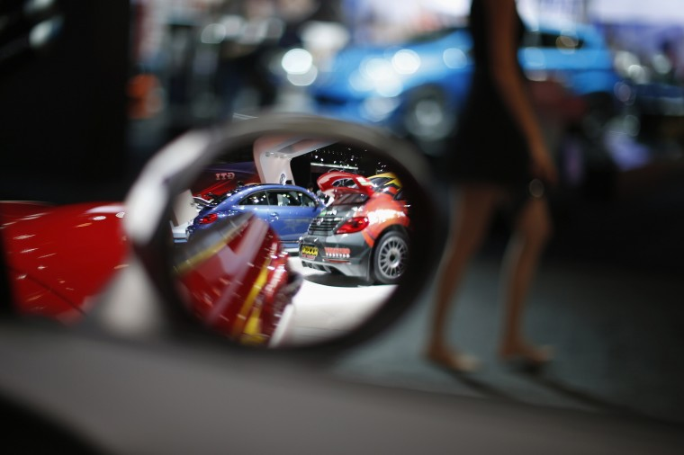 A booth model walks barefoot carrying her high heels past a Mini at the 2014 Los Angeles Auto Show in California, November 20, 2014. (Lucy Nicholson/Reuters)