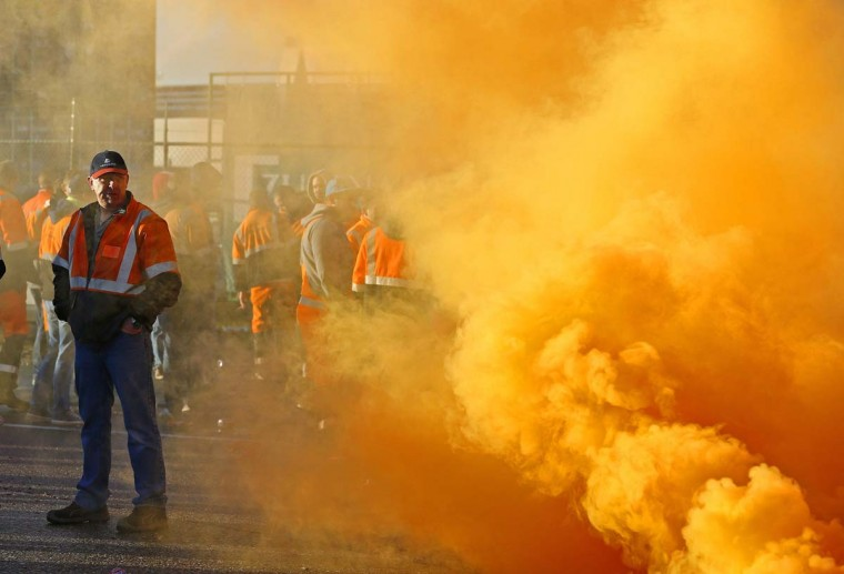 Workers, near smoke from a flare, block an entrance of the port of Antwerp, one of the world's biggest port, during a strike in Antwerp November 24, 2014. A strike in parts of Belgium on Monday disrupted rail services and one of Europe's largest ports as trade unions and workers voice their anger over austerity measures announced by the country's new government. (Yves Herman/Reuters)