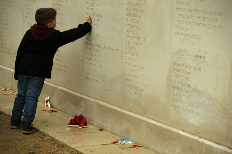 Five year old Lewis North touches a name engraved on the Armed Forces Memorial during Armistice Day commemorations at the National Memorial Arboretum in Alrewas, central England November 11, 2014. (Phil Noble/Reuters photo)