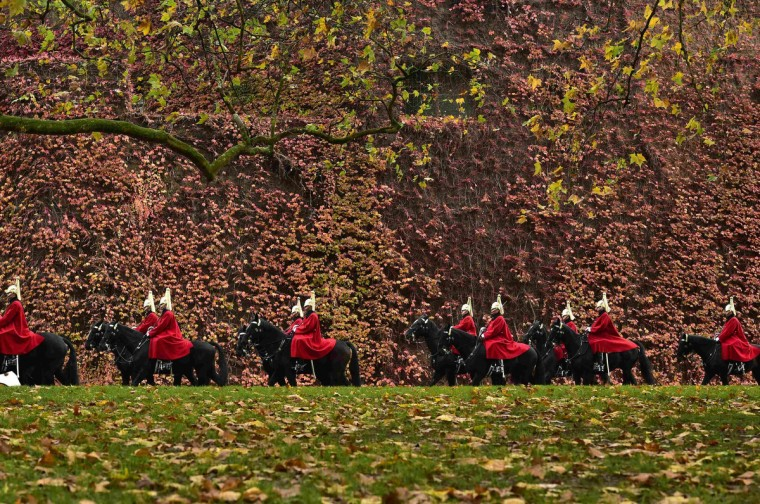 Members of the Queen's Life Guard ride along Horse Guards Road in front of foliage in autumn color during the Changing of the Guard ceremony in central London. (Toby Melville/Reuters)