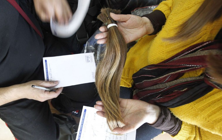 Pamela Matus (R) holds locks of her hair as stylist Marcelo Avatte (L) writes down the characteristics, for the making of a natural hair wig for a girl undergoing chemotherapy for cancer, in Vina del Mar, August 8, 2014. The wigs, handmade by Italian-Chilean hair stylist Marcelo Avatte and his team, have helped the children regain their self-esteem and confidence during cancer treatment. Renowned for making customized wigs, Avatte has donated more than 300 wigs since 2009 and says he was motivated to begin the project by the pain he felt when his own son lost his hair during chemotherapy. (Rodrigo Garrido/Reuters)