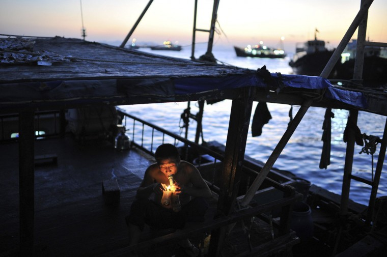 A fishman smokes on his boat, at Wai Lingting Island, east of Zhuhai, Guangdong province, November 24, 2014. Wai Lingting, with an area of 4.32 square km, is a small island located in between Zhuhai city and Hong Kong. Picture taken November 24, 2014. (REUTERS/Stringer)