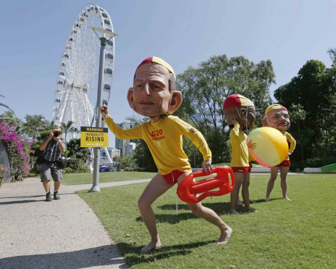 A protester, wearing a mask depicting Australian Prime Minister Tony Abbott, and dressed as a surf lifesaver calls for global equality among nations among other protesters outside the venue site of the annual G20 leaders summit in Brisbane, November 14, 2014. Leaders of the top 20 industrialized nations will gather in Brisbane November 15-16 for their annual G20 summit. (Jason Reed/Reuters)