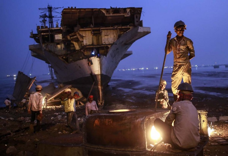 A worker uses metal cutter as others carry to dismantled parts of decommissioned Indian Navy Ship INS Vikrant at a ship breaking yard in Mumbai November 24, 2014. (Danish Siddiqui/Reuters)