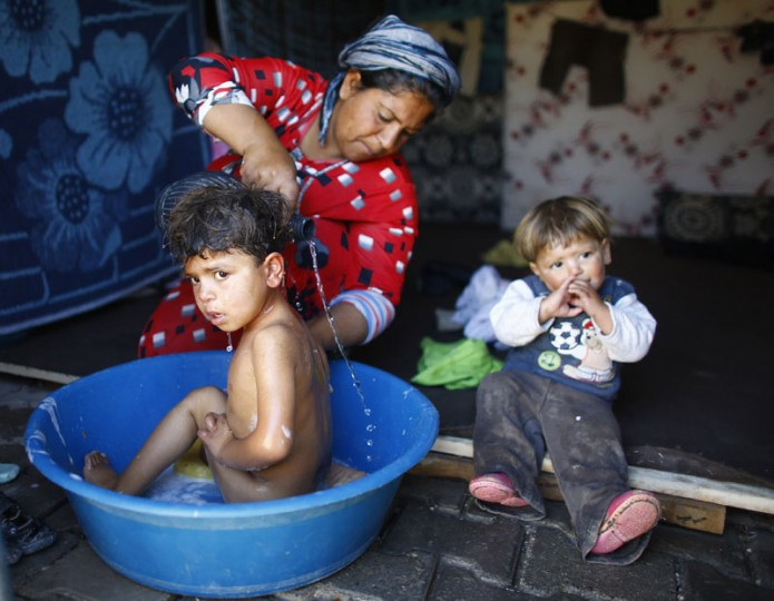A Kurdish refugee woman from the Syrian town of Kobani washes her daughter at a refugee camp in the border town of Suruc, Sanliurfa province November 18, 2014. (Osman Orsal/Reuters)
