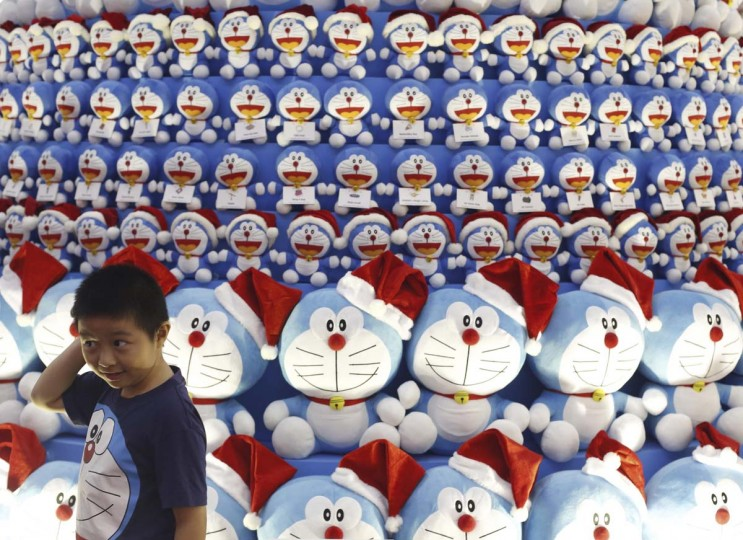 A boy wearing a Doraemon t-shirt poses for photo at a Christmas tree made up of Japanese Manga character Doraemon at a shopping mall in the central business district in Singapore, (/Edgar Su/Reuters)